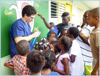 Trinity Student helps entertain the children after triage