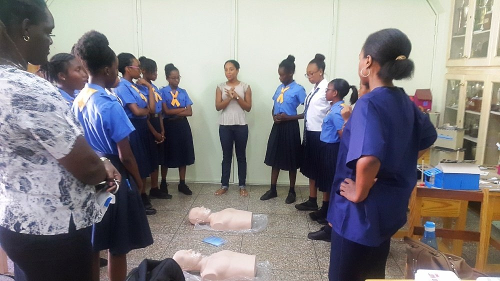 Trinity students instructing Girl Guides on basic CPR