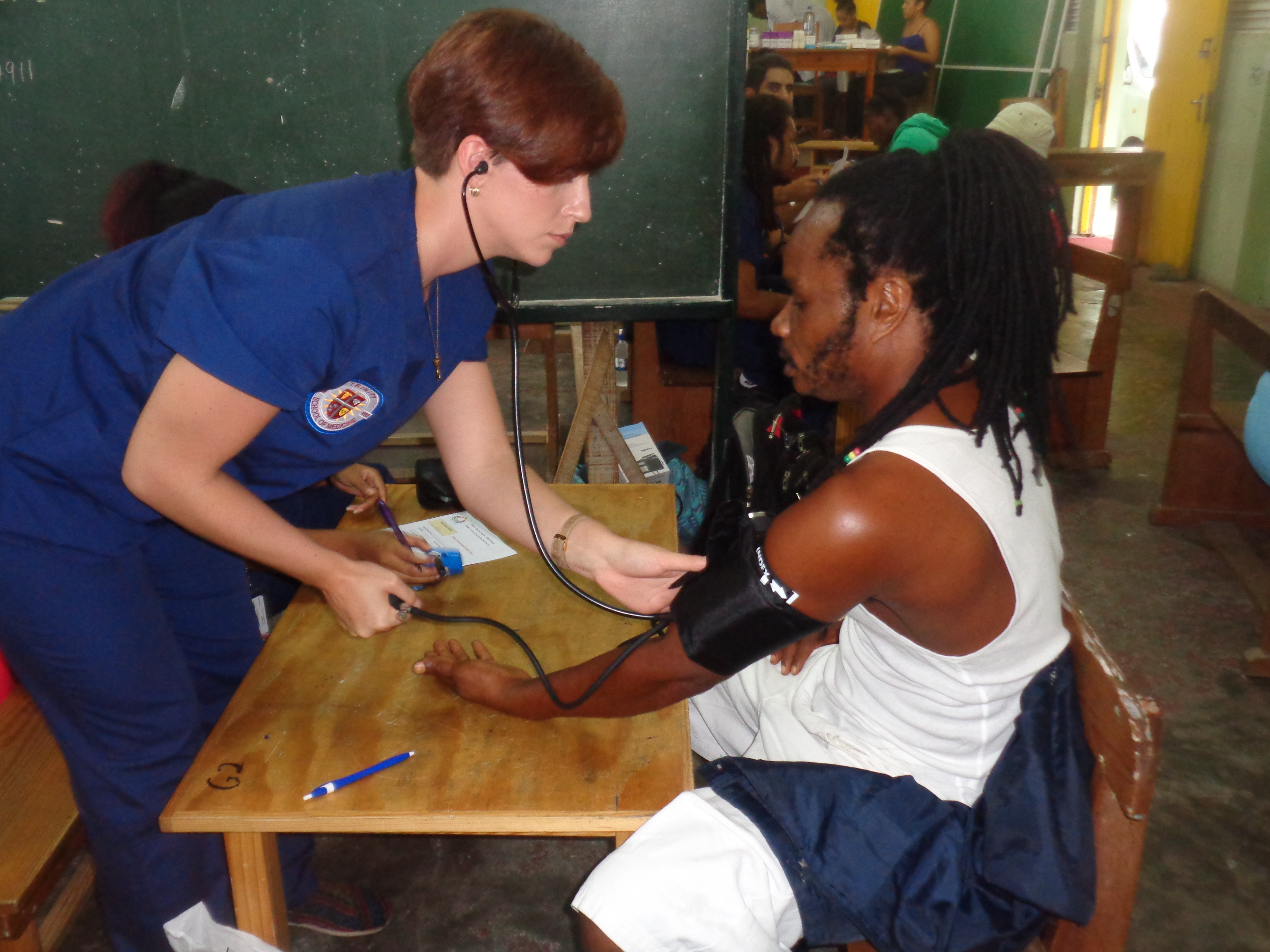 Trinity School of Medicine Student works with a patient on a medical mission trip
