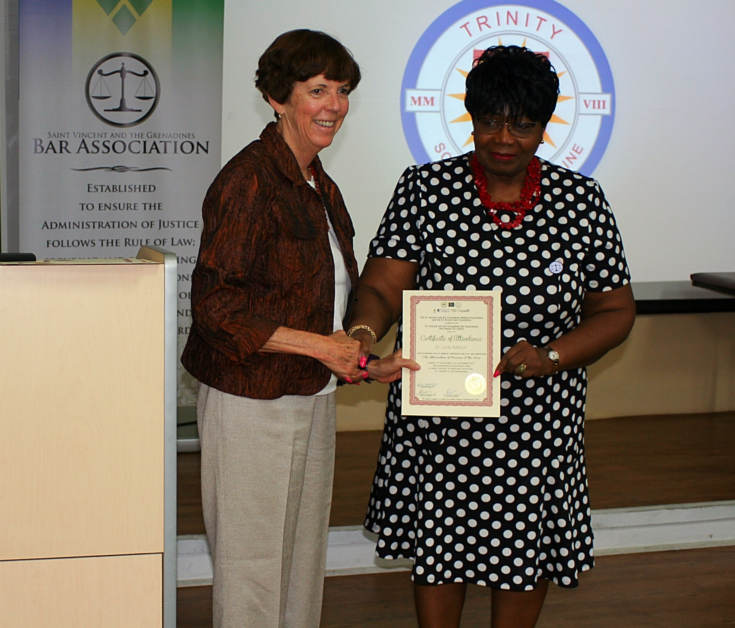 Dean Adkison receives her certificate of participation at the symposium