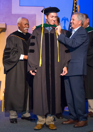 Dr. Brian Clare proudly hooding Trinity's first emergency medicine resident, his son, Dr. Drew Clare.