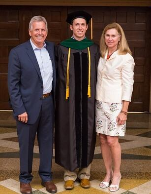 Drew with his parents graduating from Trinity School of Medicine