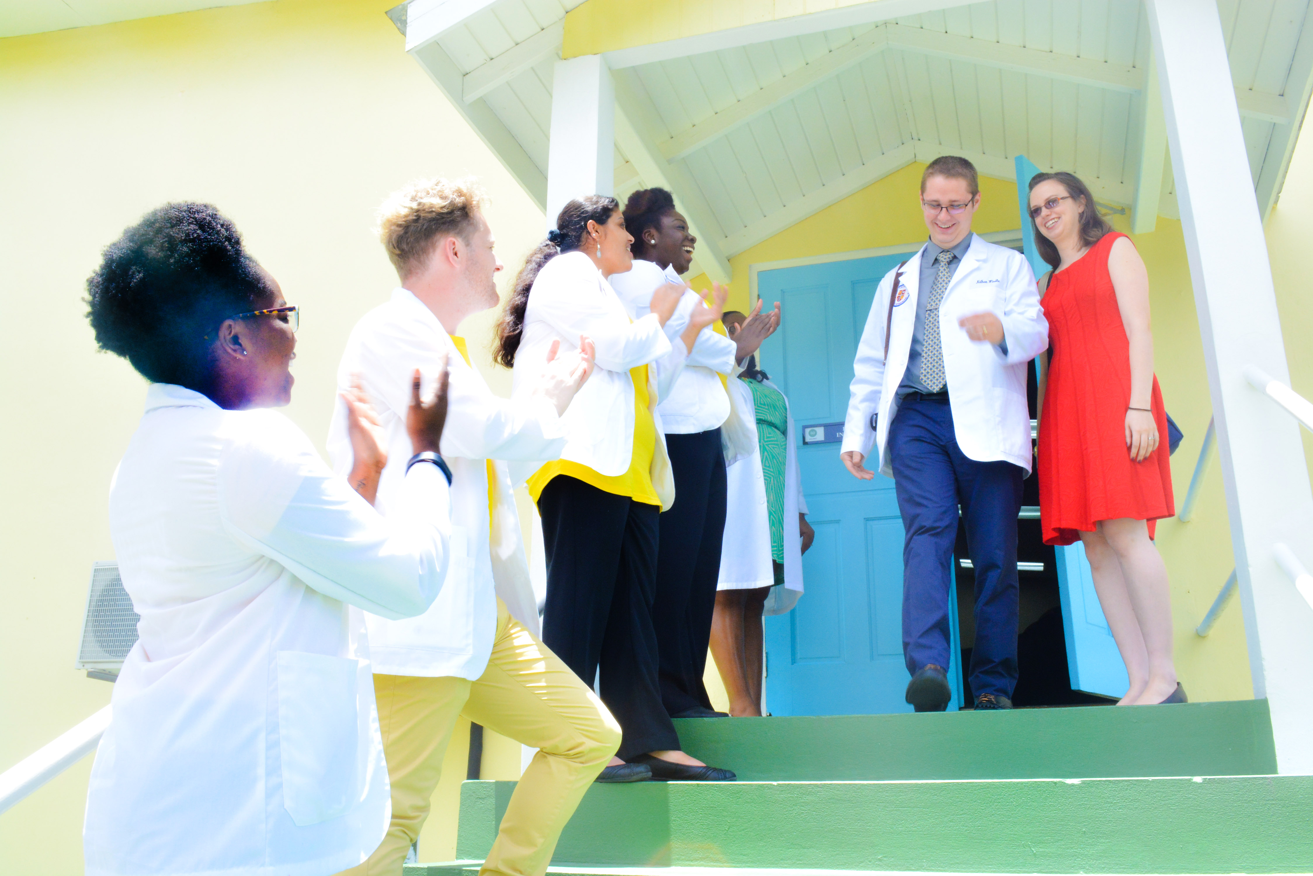 Newly minted white coat students at Trinity School of Medicine celebrate