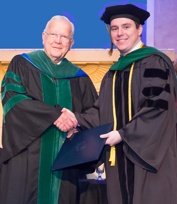 Dr. Saling shakes hands with Trinity chancellor Dr. Skelton